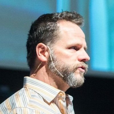 Profile photo of Derek speaking at a conference, wearing a discreet over the ear microphone